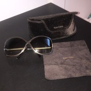 Women's black and shiny gold Tom Ford sunglasses.